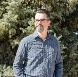 Jeff Bradshaw, looking to the left. He has dark hair and facial hair and thick rimmed glasses. He is wearing a blue striped shirt and standing in front of an evergreen