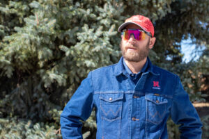 Nevin, looking left of the camera. He has a red cap, red sunglasses and a blue denim button-down on. He stands in front of an evergreen tree.