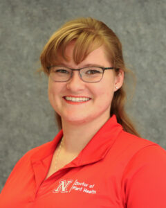 Emily smiling at the camera with a red polo shirt with the Nebraska N logo. Her hair is pulled back with bangs and is wearing square-ish glasses.